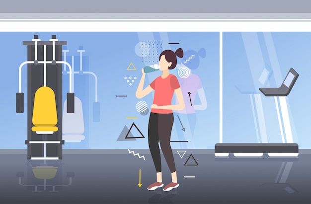 Beautiful fitness athlete woman drinking water from plastic bottle after workout exercising healthy lifestyle concept modern gym interior horizontal full length Premium Vector