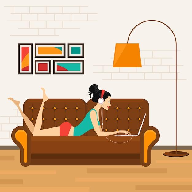 Bella ragazza sdraiata sul divano con il computer portatile e ascoltare musica in cuffia. Vettore gratuito