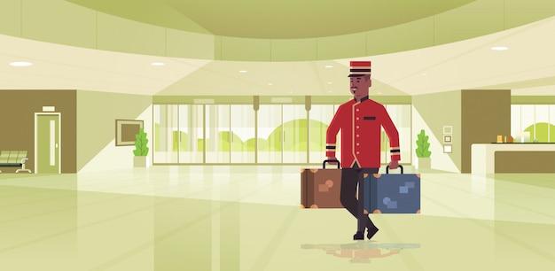 スーツケースホテルサービスコンセプトアフリカ系アメリカ人のベルマンが均一なモダンなレセプションエリアのロビーのインテリアで荷物の男性労働者を保持しているベルの少年 Premiumベクター