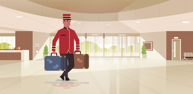 スーツケースを運ぶベル少年ホテルサービスコンセプトベルマンは均一なモダンなレセプションエリアのロビーのインテリアで荷物の男性労働者を保持 Premiumベクター