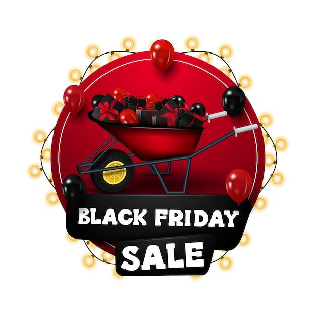 ブラックフライデーセール、花輪で包まれた赤い円の割引バナー、プレゼントと風船が付いた手押し車で飾られています。分離された割引バナー Premiumベクター