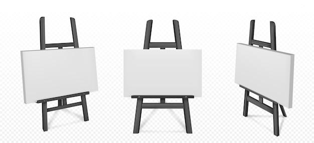正面と角度のビューで白い帆布と黒い木製イーゼル。絵画用の空白のボード、透明な背景に分離されたアートを描くための三脚と木製スタンドのリアルなモックアップ 無料ベクター