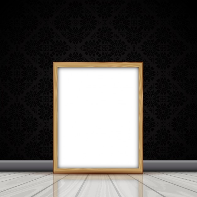 Blank picture with wooden frame leaning against a wall with damask ...