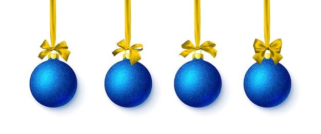 黄色の弓と青い光沢のあるキラキラ輝くクリスマスボール Premiumベクター