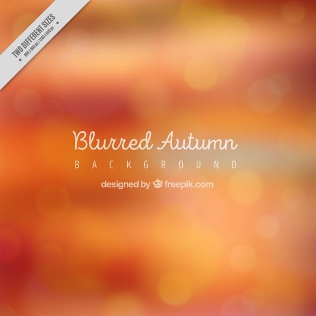 Blurred autumn background in orange tones Free Vector