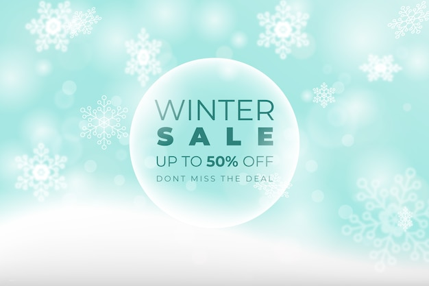 Blurred winter sale concept and snowflakes Free Vector