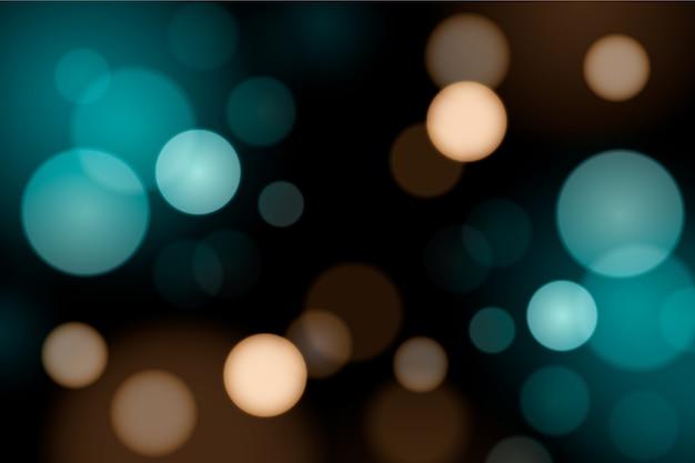 Bokeh gradient blue lights on dark background Free Vector