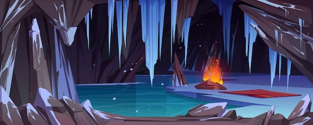 Falò nella grotta di ghiaccio scuro con neve, acqua ghiacciata e cristalli ghiacciati. Vettore gratuito