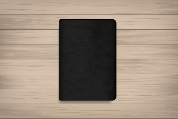 Book with black cover on wood. Premium Vector