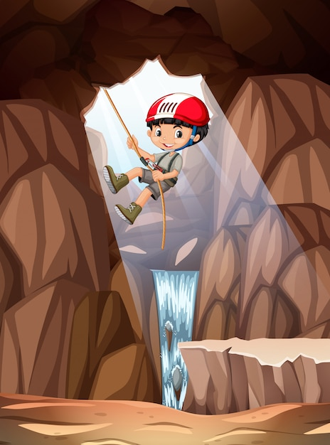 Boy abseiling into cave