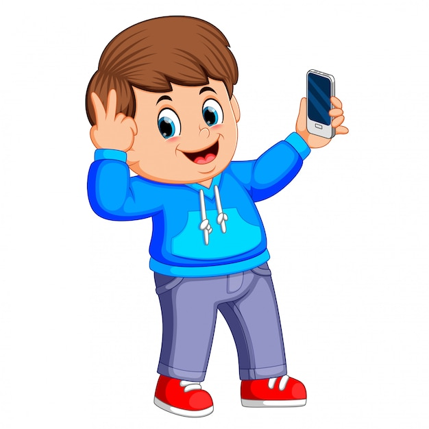 Boy holding his smartphone with his hand and taking a selfie of himself Premium Vector