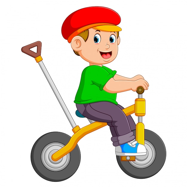 The boy is cycling on the yellow bicycle with the holder Premium Vector