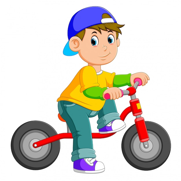 The boy is posing on the red bicycle Premium Vector