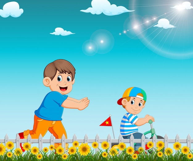 The boy is running to his brother who riding the bicycle in the garden Premium Vector