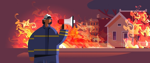 Brave fireman holding loudspeaker firefighter in uniform and helmet firefighting emergency service extinguishing fire concept burning house exterior orange flame portrait Premium Vector