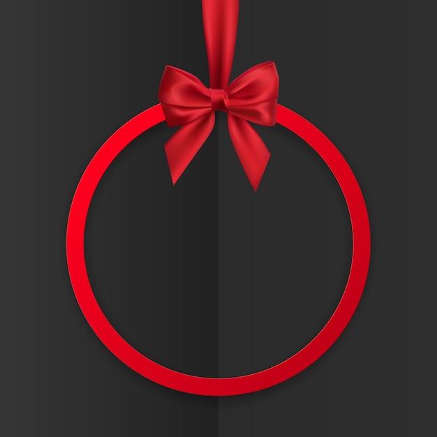 Яркий праздник круглая рамка баннер висит с красной лентой и шелковистым бантом на черном фоне. Premium векторы