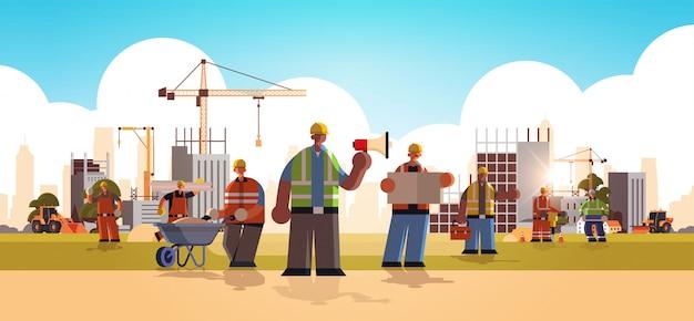 유니폼 건물 개념 건설 사이트 배경 평면 전체 길이 가로 그림에서 혼합 경주 산업 노동자를 함께 서 하드 모자 바쁜 노동자를 입고 빌더 팀 프리미엄 벡터