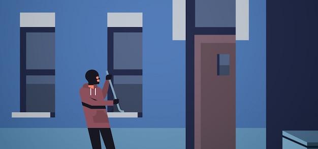 Burglar in black mask using crowbar Premium Vector