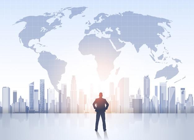 Business man silhouette over city landscape world map modern office buildings Premium Vector