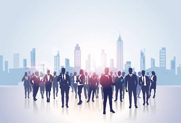 Business people group silhouettes over city landscape modern office buildings Premium Vector