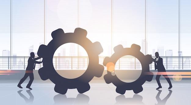Business people pushing cogwheel brainstorming process teamwork Premium Vector