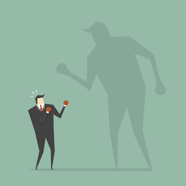 Businessman boxing with a shadow Free Vector