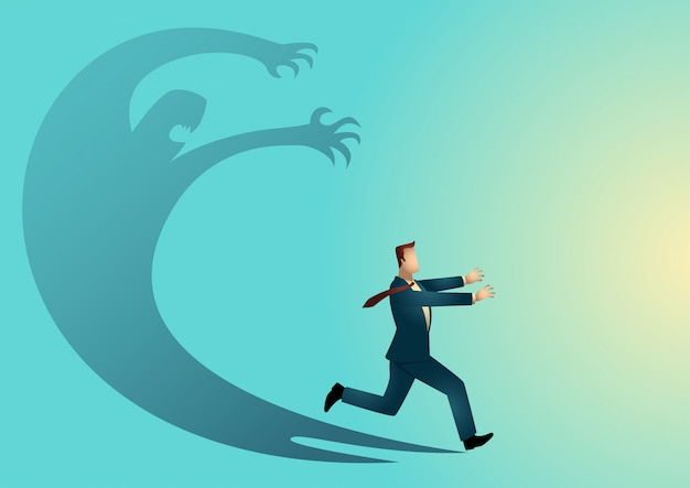 Businessman frightened with his own shadow Premium Vector