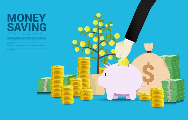 Businessman hand put coin in piggy bank with money tree of coin background Premium Vector