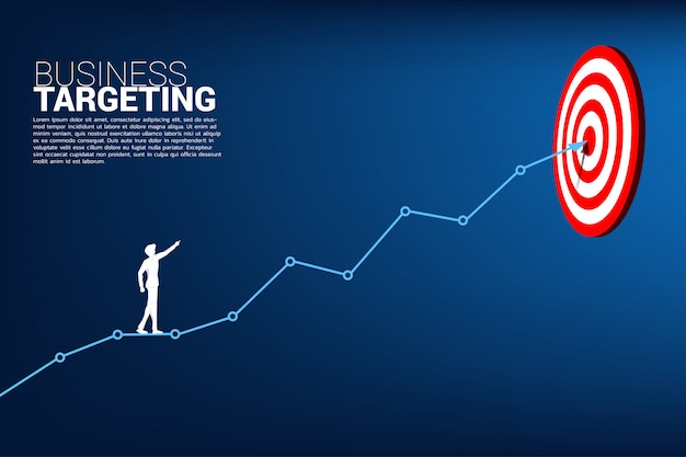 Businessman point to dartboard on line graph to center Premium Vector
