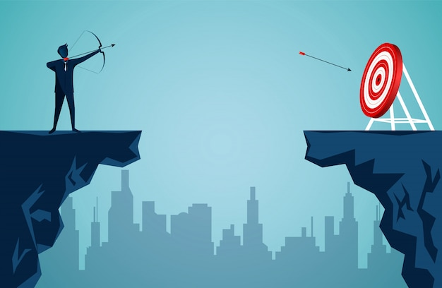 Businessman standing on cliff is shooting an arrow across the cliff opposite the arrow to the target in the center of the red circle Premium Vector