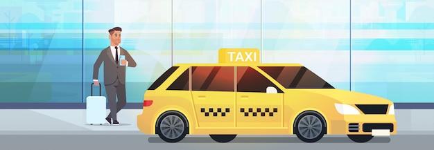 黄色のタクシーの都市交通サービスの近くの荷物とフォーマルな服装でストリートビジネスの男性にモバイルアプリ注文タクシーを使用するビジネスマン Premiumベクター