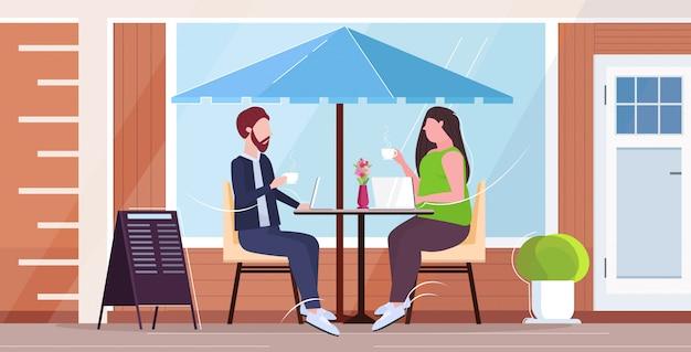 Бизнесмены пара обсуждая во время встречи бизнесмены человек женщина сидя за столом выпивая концепция связи кофе улица улица экстерьер полно горизонтальный Premium векторы
