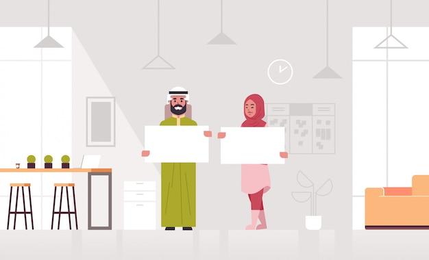 Ключевые слова на русском: бизнесмены пара пустой пустой вывеска арабский бизнес мужчина женщина партнеры показаны пустой белый картон реклама концепция интерьер офис полная длина горизонтальный Premium векторы