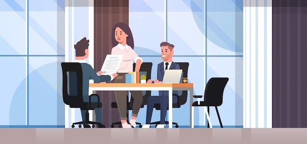 Деловые люди обсуждают контракт во время развития бизнеса встречаются коллеги партнеры работают с интерьером офиса переговоров по соинвестированию документов Premium векторы