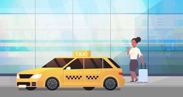 黄色いタクシー都市交通サービスコンセプト全長水平近く荷物とフォーマルな服装でストリートビジネス女性にタクシーを注文するモバイルアプリを使用して実業家 Premiumベクター