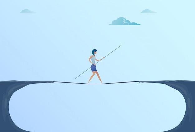 Businesswoman walk over cliff gap mountain business woman balancing wooden stick bridge Premium Vector