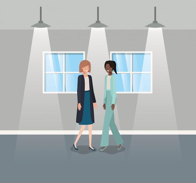 Businesswomen couple in corridor office Premium Vector