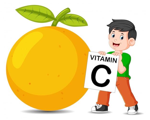 オレンジの横にある少年はビタミンcボードを持っています Premiumベクター