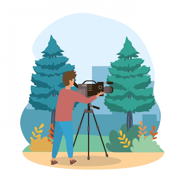 Camera man with camcorder equipment and pines trees with bushes Premium Vector