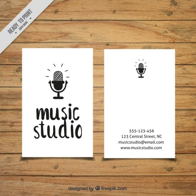 Card with a microphone drawn to a music studio Free Vector