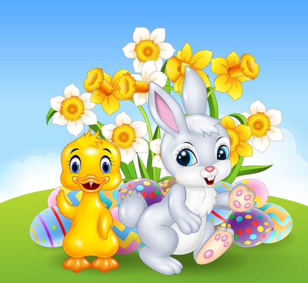 Cartoon happy duck and bunny with colourful easter eggs Premium Vector