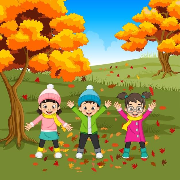 Мультфильм счастливые дети, играющие на осеннем фоне Premium векторы