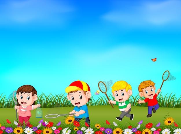 Cartoon kids catching butterfly in the garden Premium Vector