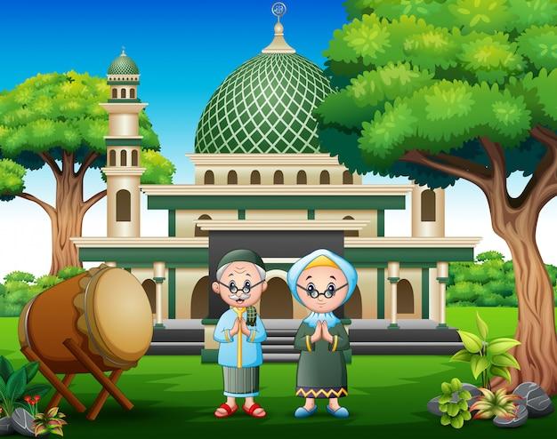 Cartoon old couple muslim in front the mosque Premium Vector