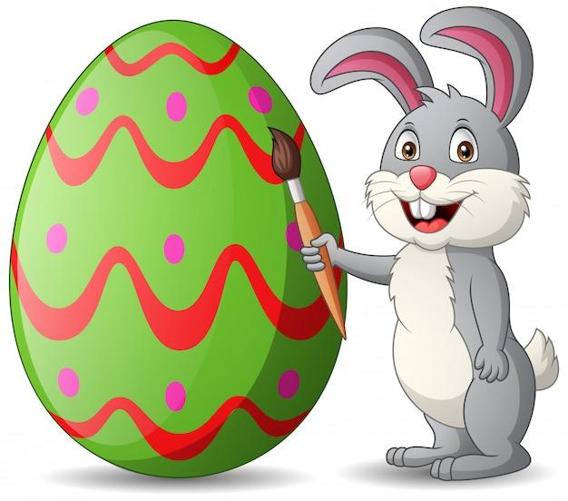 Cartoon rabbit is painting eggs. illustration Premium Vector