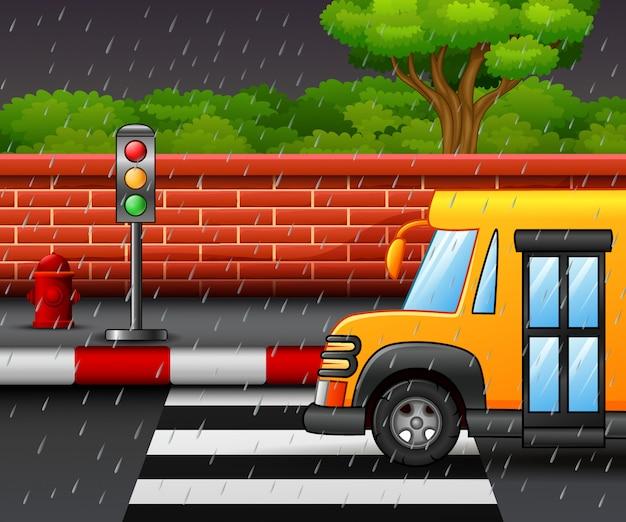 Cartoon of road scene with school bus and heavy rain Premium Vector