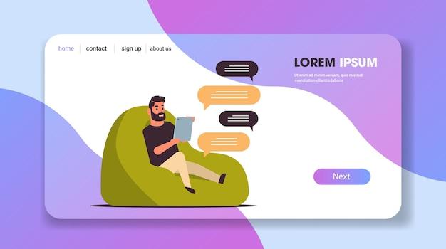 カジュアルな男がモバイルアプリのソーシャルネットワークチャットバブル通信を使用してビーンバッグに座っているタブレット男とメッセージングをチャット Premiumベクター