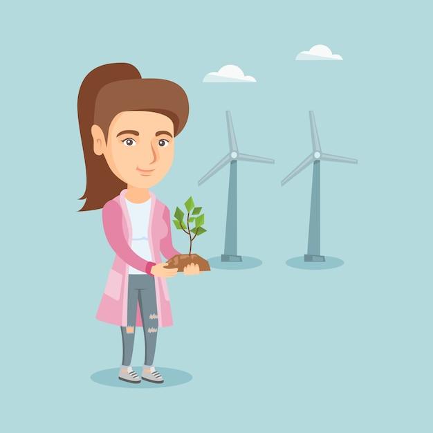 Caucasian worker of wind farm holding small plant. Premium Vector