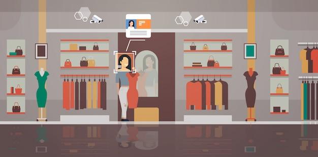 新しいドレス衣料品店の顧客識別顔認識モダンブティックインテリアセキュリティカメラ監視cctvシステムを試す女性 Premiumベクター