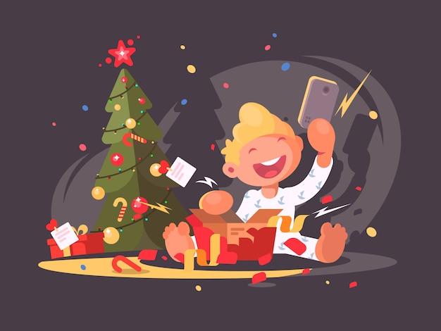 子供はクリスマスプレゼントを開きます。ギフト用の箱のスマートフォン。図 Premiumベクター